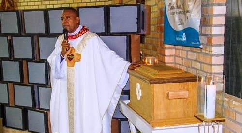 O padre lavrense Vicente de Paula ao lado da urna com os restos mortais de Padre Léo na Casa Mãe da comunidade Bethânia, em São João Batista (SC).